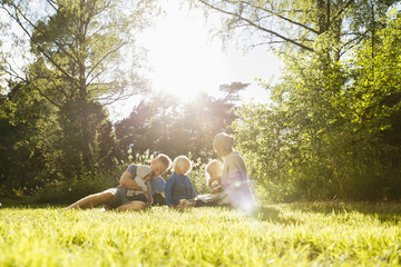 Sweden, Sodermanland, Trosa, Family with children (6-11 months, 2-3, 4-5) sitting on grass