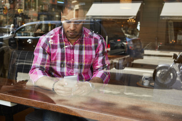Sweden, Mature man checking his mobile phone inside cafe