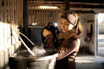 Sweden, Uppland, Faringso, Woman pouring water from watering can to bucket