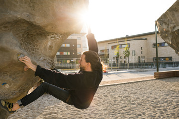 Sweden, Skane, Malmo, Man climbing on climbing wall