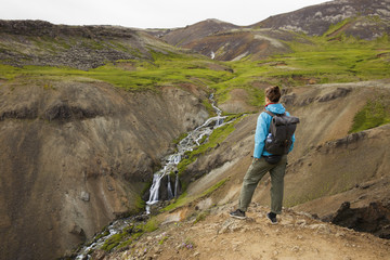 Iceland, Sudurland, Hveragerdi, Reykjadalur, Tourist looking at stream and waterfalls in rocky valley