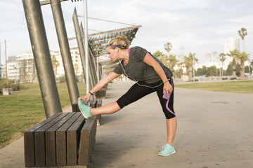 Israel, Tel Aviv, Young blonde woman stretching on bench