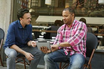 Sweden, Mature men looking at digital tablet in sidewalk cafe