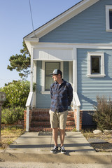 USA, California, Pacific Grove, Mature man standing in front of blue house