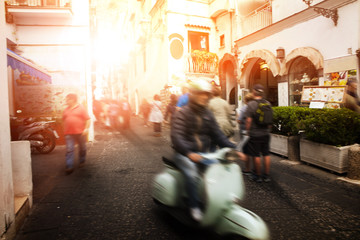 man riding scooter motorcycle in amalfi street south italy most popular traveling destination
