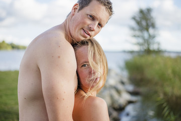 Sweden, Vastmanland, Portrait of shirtless mid adult couple embracing by lake