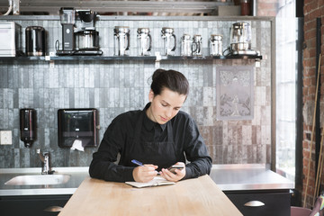 Norway, Young woman working at coffee shop with cell phone and notebook