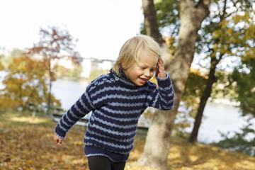 Sweden, Sodermanland, Stockholm, Sodermalm, Langholmen, Blonde boy (2-3) laughing in autumn park