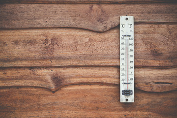 Wood thermometer calibrated in degrees celsius on the wooden wall, concept of world hot and weather.