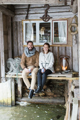 Sweden, Young couple sitting on wooden table