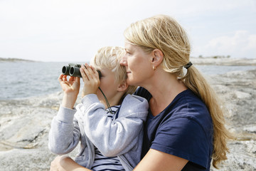 Sweden, Stockholm Archipelago, Sodermanland, Orno, Mother and son (6-7) sitting on rocky seashore, son looking through binoculars