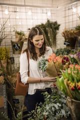 Sweden, Woman choosing flowers in shop
