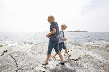 Sweden, Stockholm Archipelago, Sodermanland, Orno, Two boys (6-7, 8-9) walking on rocky seashore