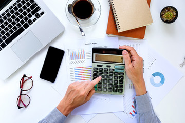 Business man hands working on calculator with financial data on office desk table .View from above.Business analysis and strategy concept.