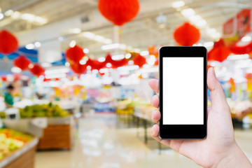 Woman using mobile smartphone while shopping in supermarket store