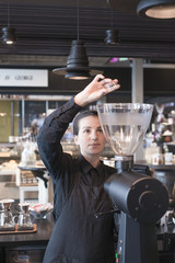 Norway, Young woman preparing coffee at coffee shop