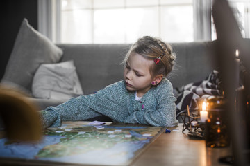 Sweden, Girl (4-5) playing board game on coffee table