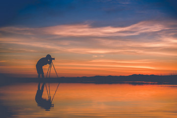 Silhouette Photographer take photo beautiful seascape at sunset in Thailand