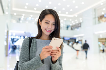 Woman use of mobile phone in shopping mall