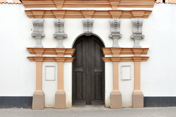 Arched wooden door of an old white  building. Church of St. Brigid, Grodno, Belarus.