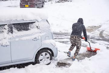 Fresh white snow falling at public park cover road and car in winter season at Kawaguchiko,Japan.