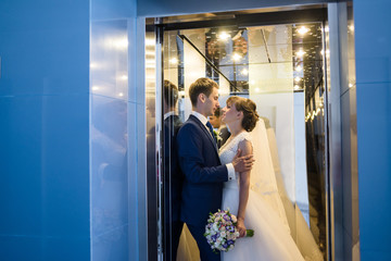 Groom and bride are kissing in hotel interior