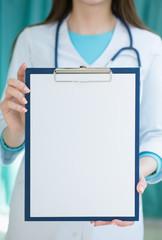 Medical doctor holding folder for notes in hands