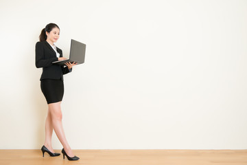 business woman using laptop computer with white wall