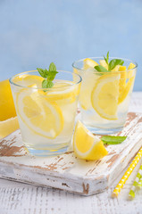 Cold refreshing summer drink with lemon and mint on wooden background. Selective focus, copy space.