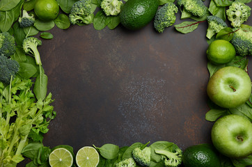 Variety of green fruits and vegetables on a dark concrete, stone or slate background. Top view, copy space.