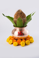 copper kalash with coconut and mango leaf with floral decoration. essential in hindu puja, front view, closeup