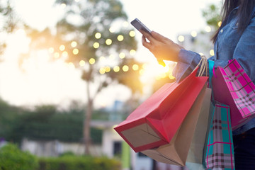 Woman using smartphone with shopping bags in hands