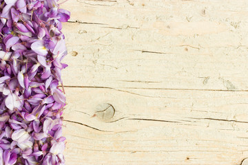 Border made of violet wisteria flowers on white wooden background. Top view with copy space.