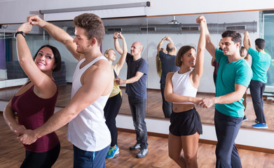 Adults dancing bachata together in dance studio
