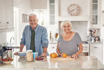 Smiling seniors preparing a healthy breakfast together at home