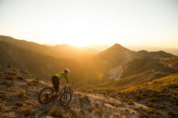 Cyclist man riding mountain bike at sunset