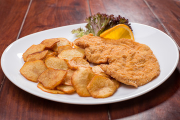 Plate with fried poultry breast with fried potatoes