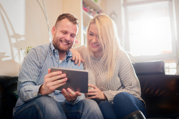 Happy couple smiling and sitting on sofa in living room. They using tablet