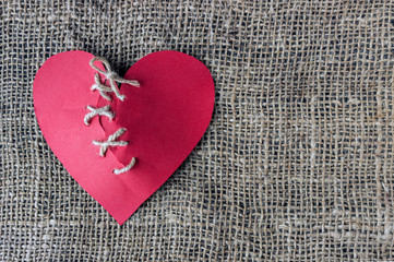 A broken red heart. Sewn thread. The concept of divorce, separation.