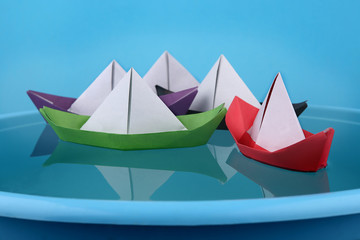 Paper boats game. Origami paper ships sailing on blue water surface.