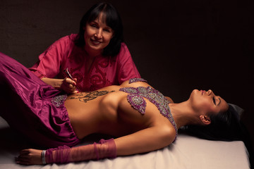 White woman a mehendi artist paints an ornament of henna on an eastern beautiful girl's stomach