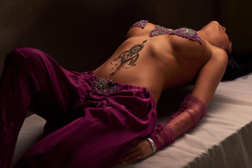 Eastern beautiful brunette woman with mehendi on her stomach