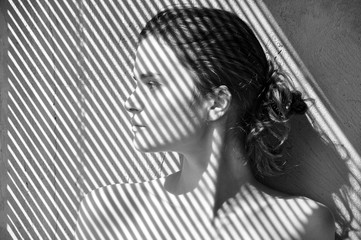 Black and white portrait of a young European girl in profile against a grunge wall with a striped shadow from the blinds.
