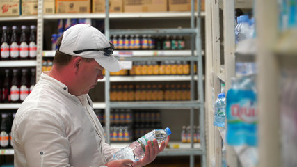man buys mineral water in supermarket or store.