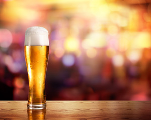 Golden Beer In Glass With Lights Of Bar In Background