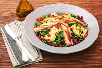 Salad with fried salmon, avocado and pomegranate seeds