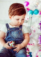 Thoughtful child plays with toy sitting before Christmas tree