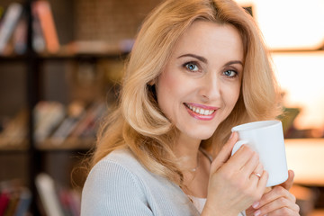 Beautiful blonde mature woman drinking tea and smiling at camera