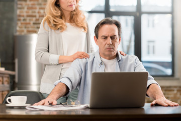 Cropped shot of blonde woman standing behind upset husband using laptop at home