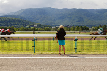 Horse racing. The woman at the racetrack looks at the galloping horses. Shot of a man without a face standing with his back
